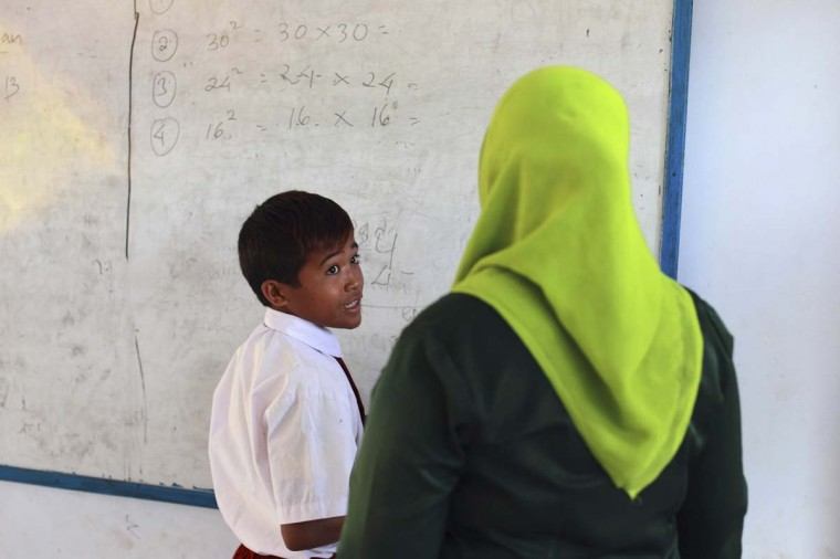 Endiansyah Mohammad (L) talks to his teacher during class in Dompu. Dozens of child jockeys, some as young as eight-years-old take part in the races. Picture taken November 20, 2012. (Beawiharta/Reuters)