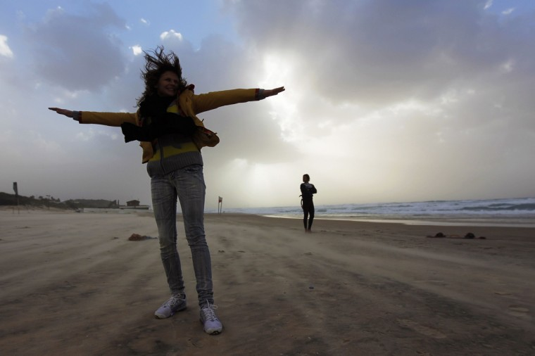 A woman raises her arms on a windy day at the beach in the southern Israeli city of Ashkelon. Winds reached speeds of up to 35 knots along the coast in Israel. (Amir Cohen/Reuters photo)