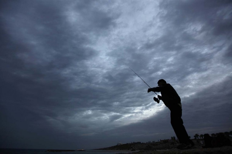 An Israeli man fishes in the Mediterranean sea after sunset at a beach in the southern city of Ashkelon December 3, 2012. (Amir Cohen/Reuters)
