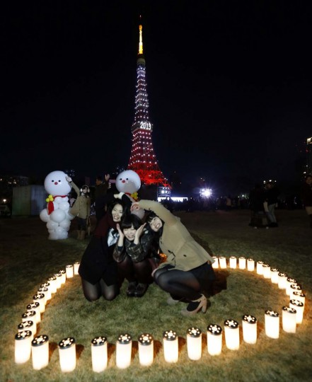 People take a picture in front of the Tokyo Tower which is illuminated to celebrate the New Year after a countdown event in Tokyo January 1, 2013. (Kim Kyung-Hoon/Reuters)