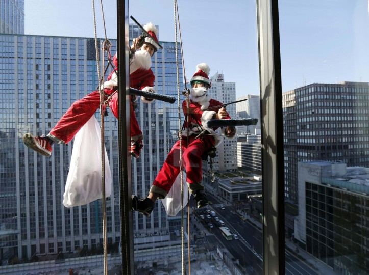 Window cleaners dressed as Santa Claus work during an event promoting Christmas at a hotel in the business district of Tokyo. (Kim Kyung-Hoon/Reuters photo)