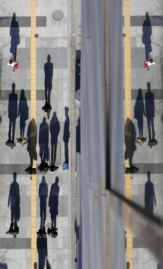 Pedestrians cast shadows on the sidewalk near the headquarters of the Bank of Japan in Tokyo. The Bank of Japan eased monetary policy by expanding its asset-buying and lending program, a widely expected move in response to intensifying pressure from incoming premier Shinzo Abe to confront chronic deflation. (Kim Kyung-Hoon/Reuters photo)