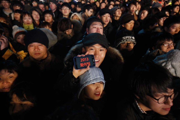 "A man holds his phone showing a message that says ""cheer up 2013"" as people gather to welcome the new year near the Bosingak pavilion in central Seoul December 31, 2012. (Kim Hong-Ji/Reuters)"