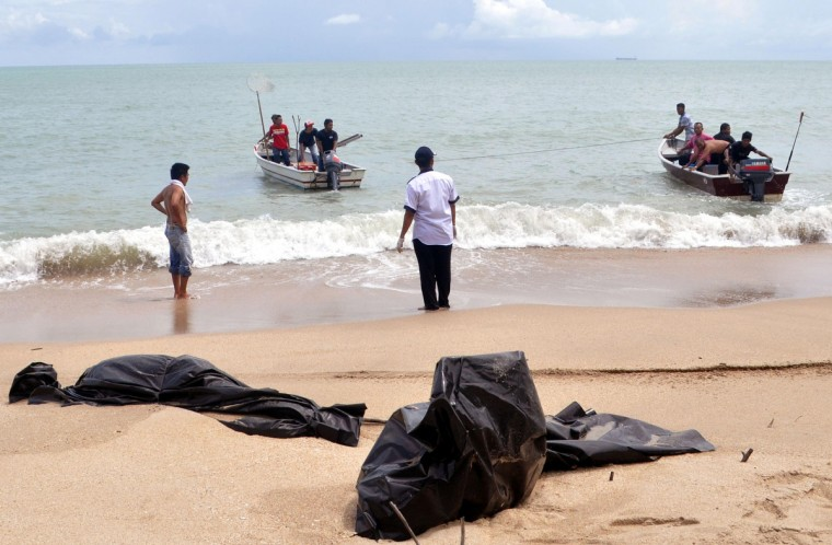 Malaysian authority personnel collect bodies on the beach in Bandar Penawar. Malaysia's marine police have recovered at least 11 bodies, believed to be Indonesians, that were washed ashore in the southern coast of Malaysian peninsular, as reported by The Star daily. (Stringer/Reuters photo)