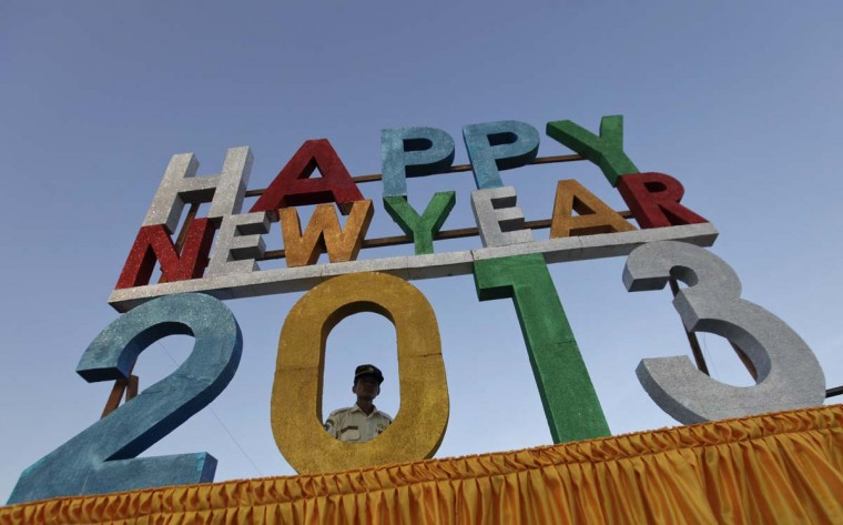 A security guard stands behind a New Year signboard at Myanmar's first public New Year countdown celebrations on Myoma grounds in Yangon December 31, 2012. (Soe Zeya Tun/Reuters)