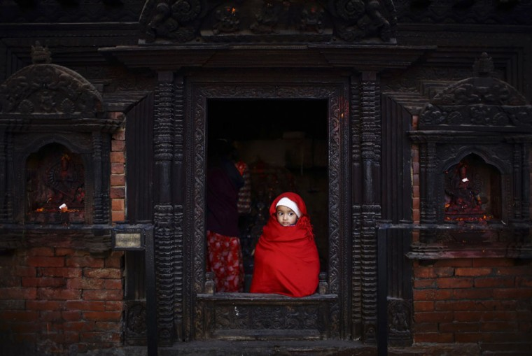 A girl looks out from the entrance door of a temple as her mother offers daily prayers inside the temple in Lalitpur, Nepal. (Navesh Chitrakar/Reuters)
