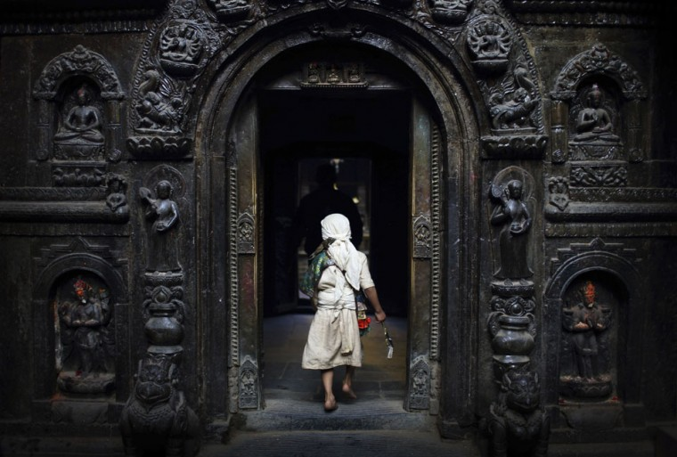 A priest enters the premises of a temple to offer daily prayers in Lalitpur, Nepal. (Navesh Chitrakar/Reuters)