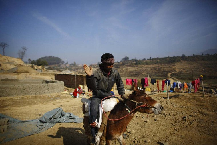 A boy slaps his donkey for not obeying his orders at a brick factory in Lalitpur December 19, 2012. (Navesh Chitrakar/Reuters)