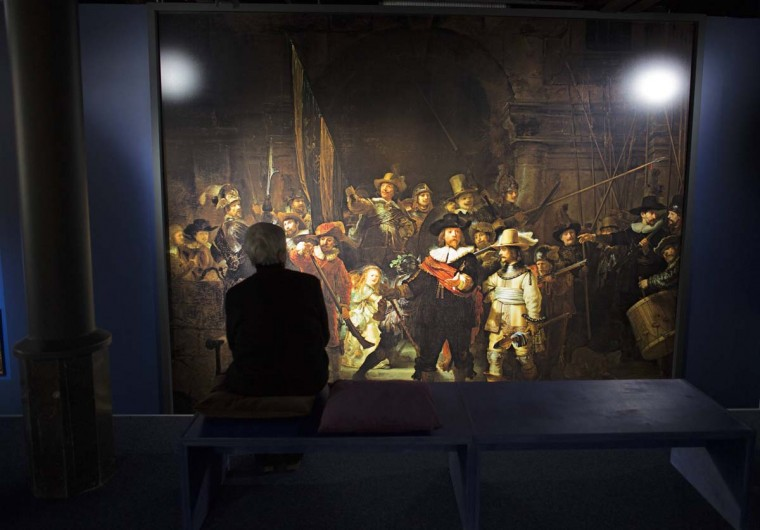 A woman studies a life size reproduction the painting entitled 'De Nachtwacht' (The Night Watch) by the Dutch painter Rembrandt van Rijn at Magna Plaza shopping center in Amsterdam December 26, 2012. Reproductions of all 325 paintings by Rembrandt will on permanent display at the shopping center. (Michael Kooren/Reuters)