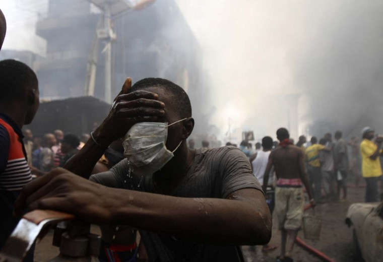 A volunteer cleans his face near the site of a fire, after fireworks stored in a building exploded in a densely populated area in the Isale Eko district of Nigeria's commercial capital of Lagos December 26, 2012. (Akintunde Akinleye/Reuters)