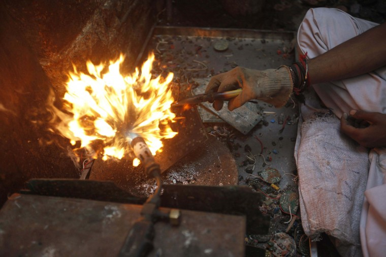 A boy heats up a computer circuit board to retrieve metal that is used to make soldering wire in a makeshift workshop in Karachi. (Athar Hussain/Reuters photo)