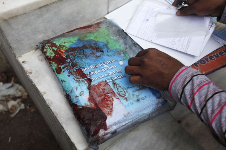 A rescue worker checks blood-stained forms which belong to Nasima Bibi, a female worker of an anti-polio drive campaign who was shot by gunmen, after the papers were brought to the hospital morgue in Karachi. Gunmen shot five health workers on the anti-polio drive in a string of attacks in Pakistan on Tuesday, officials said, raising fears for the safety of workers immunizing children against the crippling disease. (Athar Hussain/Reuters)