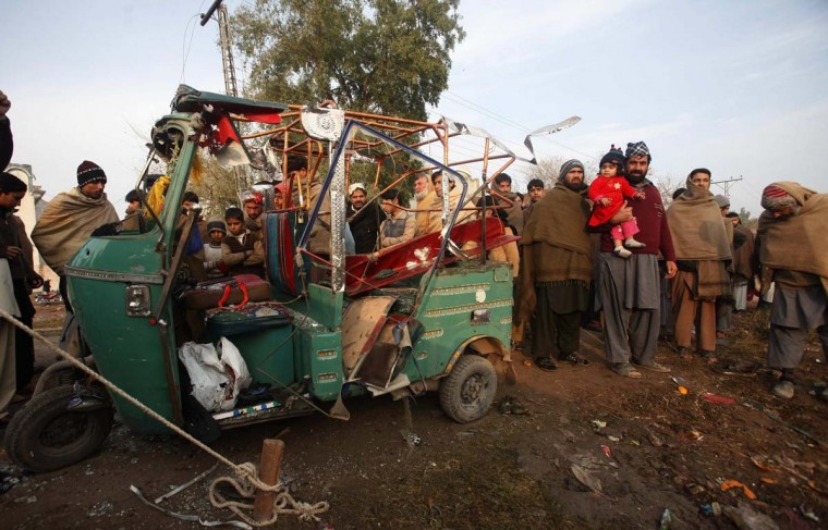 People gather around a rickshaw damaged during a rocket attack on Saturday night near a boundary wall of Peshawar's airport December 16, 2012. Four people were killed when militants attacked the airport in the northwestern city of Peshawar on Saturday and traded gunfire with soldiers for more than 30 minutes before being repulsed, military and health officials said. (Fayaz Aziz/Reuters)