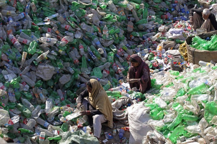 Laborers separate bottles by colour at a plastic recycling factory in Lahore, Pakistan. (Mohsin Raza/Reuters)