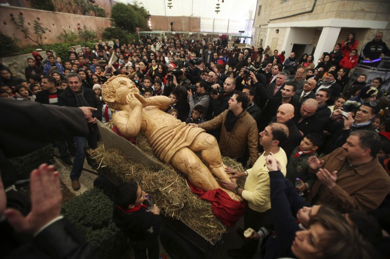Palestinians surround a cart carrying a wooden statue of Baby Jesus before a march in the West Bank town of Bethlehem ahead of Christmas. (Mohamad Torokman/Reuters photo)
