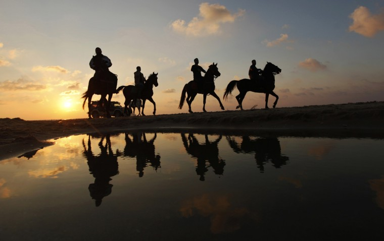 Palestinian men ride horses during sunset on the beach of Gaza City. (Mohammed Salem/Reuters)