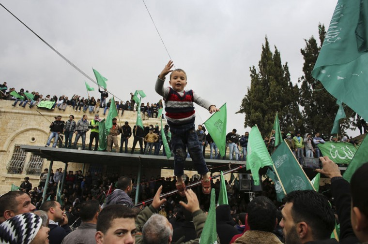 A Palestinian boy is thrown in the air as Hamas supporters wave flags during a rally in the West Bank city of Hebron, marking the 25th anniversary of the founding of the Islamist militant group. It was one of the first rallies Western-backed Palestinian President Mahmoud Abbas allowed to take place in the West Bank since 2007, when his Islamist rivals Hamas seized control of the Gaza Strip. (Ammar Awad/Reuters)