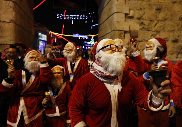 Palestinians dressed up as Santa Claus take part in a parade ahead of Christmas near Jerusalem's Old City December 16, 2012. (Ronen Zvulun/Reuters)