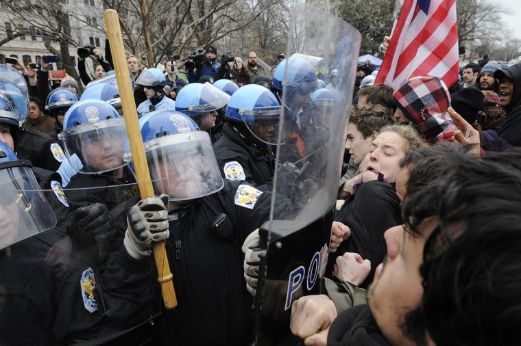 """U.S. National Park Service police move protesters out of the way to erect barricades as they clear the Occupy DC encampment in McPherson Square in Washington, February 4, 2012. Police officers wearing helmets and carrying shields arrived at the site where protesters with the """"Occupy"""" movement have been staging a demonstration since October, but it was not immediately clear whether they would evict the protesters. (Jonathan Ernst/Reuters)"""