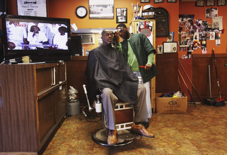 """Mustafa Bey gets his haircut from barber Habib Ahad at """"A Whole Nu Look"""" barbershop near Whitney Houston's funeral at Hope Baptist Church in Newark, New Jersey February 18, 2012. Houston, 48, died in a Beverly Hills hotel room on February 11, the eve of the industry's Grammy Awards. (Shannon Stapleton/Reuters)"""