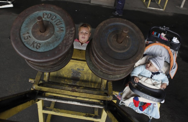 Simone Franco, 35, lifts weights next to her 11-month-old son Aquiles Franco (R) at a gym under the Alcantara Machado viaduct in the Mooca neighborhood of Sao Paulo July 18, 2012. Alcantara Machado gym was founded in 2009 by Brazilian former professional boxer Nilson Garrido under the Alcantara Machado viaduct, with the aim of getting young people out of drugs and crime through sports. Currently the gym, which received all its equipment through donations, is visited daily by more than a hundred people, most of whom are unemployed or have financial troubles, who practice bodybuilding and other sports just for pleasure. (Nacho Doce/Reuters)