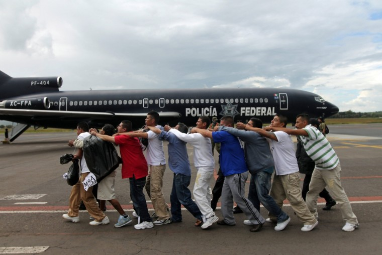 Federal policemen escort a group of prisoners toward a plane bound for an undisclosed location at the Morelia International Airport August 21, 2012. Some 200 inmates serving federal sentences were transferred to federal prisons during an operation by the Secretary of Public Security (SSP), local media reported. (Leovigildo Gonzalez/Reuters)