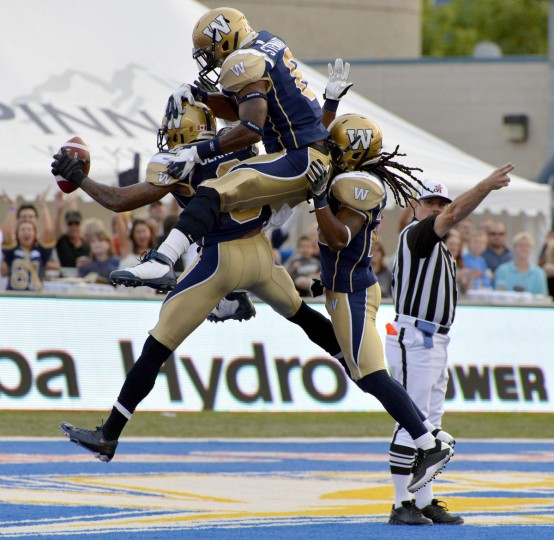 Winnipeg Blue Bombers' Johnny Sears (L) celebrates his interception against the BC Lions with Brandon Stewart (C) and Jonathan Hefney during the first half of their CFL game in Winnipeg, August 24, 2012. (Fred Greenslade/Reuters)