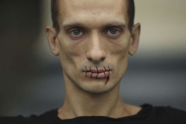 """Artist Pyotr Pavlensky, a supporter of jailed members of female punk band """"Pussy Riot"""", looks on with his mouth sewed up as he protests outside the Kazan Cathedral in St. Petersburg, July 23, 2012. A court on Monday rejected a request to call President Vladimir Putin and the head of the Russian Orthodox Church to testify in the trial of three female punk rockers who derided Putin in a protest in the country's main cathedral, their lawyer said. (Trend Photo Agency/Reuters)"""