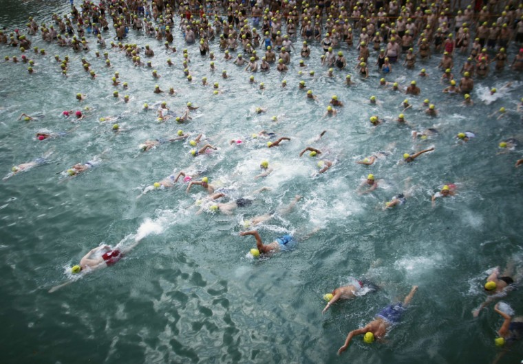 People swim at the start of the annual Lake Zurich crossing swimming event in Zurich August 22, 2012. The participants swam across Lake Zurich on a 1,500 metres (4,921 ft) track. (Michael Buholzer/Reuters)