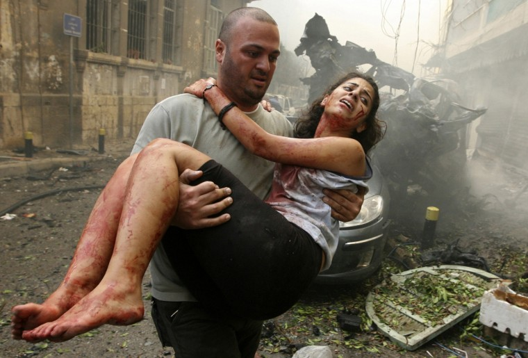 A wounded woman is carried at the site of an explosion in Ashrafieh, central Beirut, October 19, 2012. At least two people were killed and 15 wounded by a huge bomb that exploded in a street in central Beirut on Friday, witnesses and a security source said. (Hasan Shaaban/Reuters)