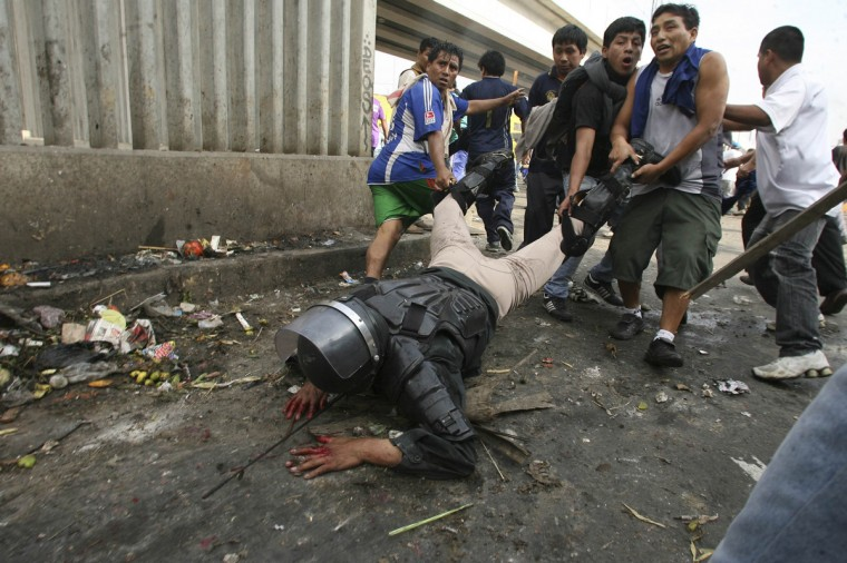 A riot police officer is dragged by protesters after being knocked down off his horse with rocks thrown by workers of 'La Parada' wholesale market in Lima, October 25, 2012. Clashes between the wholesale market workers and police officers yesterday left two people dead and more than 100 injured when concrete blocks were attempted to be placed at the entrances by local authorities to prevent market supply, according to local media. Picture taken October 25, 2012. (Alessandro Currarino/Diario El Comercio/Reuters)