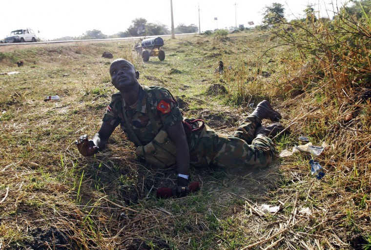 A SPLA soldier looks at warplanes as he lies on the ground to take cover beside a road during an air strike by the Sudanese air force in Rubkona near Bentiu April 23, 2012. Sudanese warplanes carried out air strikes on South Sudan on Monday, killing three people near the southern oil town of Bentiu, residents and military officials said, three days after South Sudan pulled out of a disputed oil field. (Goran Tomasevic/Reuters)