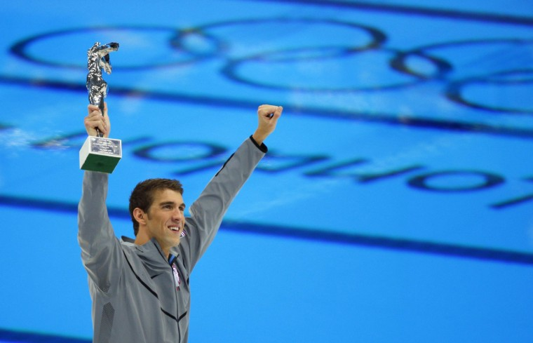 Michael Phelps of the U.S. holds up his award recognizing him as the most decorated Olympian, during the London 2012 Olympic Games at the Aquatics Centre August 4, 2012. Phelps ended his incredible Olympic career on the perfect note on Saturday, winning his 18th gold medal for the United States in the men's medley relay, the last time he will swim a competitive race. (Brian Snyder/Reuters)