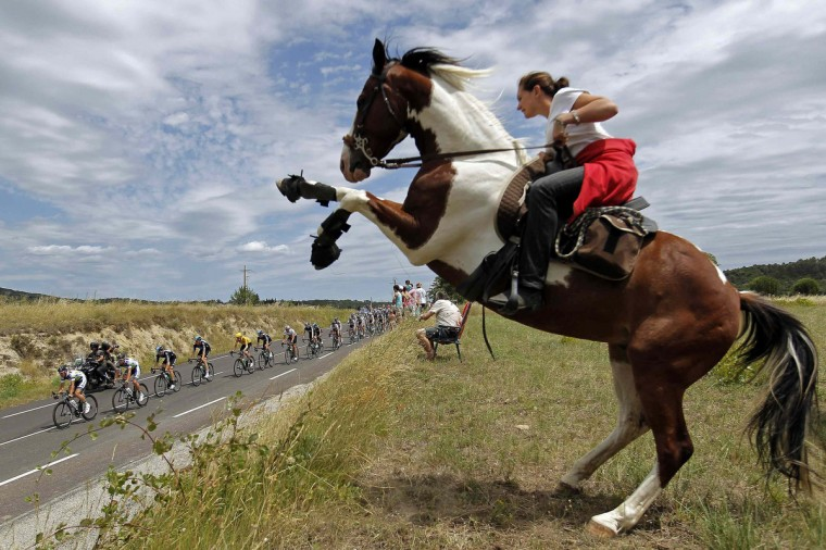 The pack of riders cycles past a woman on a horse during the 13th stage of the 99th Tour de France cycling race between Saint-Paul-Trois-Chateaux and Cap d'Agde, July 14, 2012. (Stephane Mahe/Reuters)