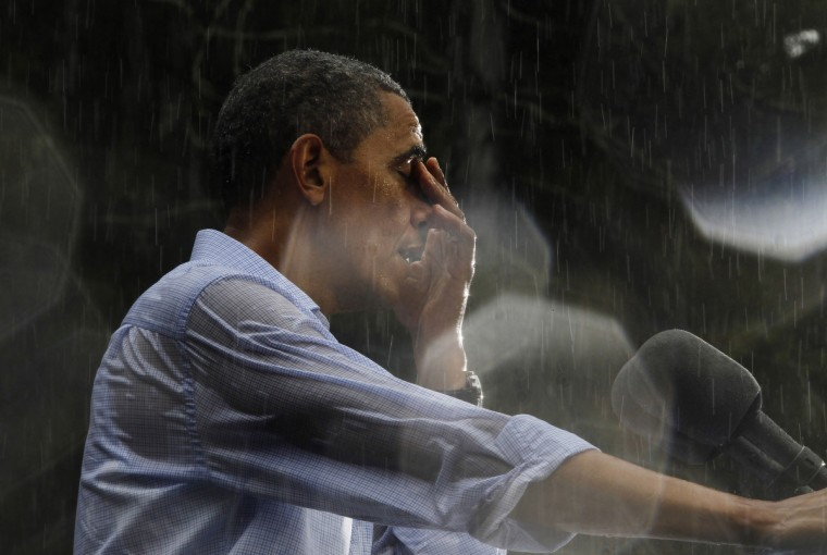 U.S. President Barack Obama wipes water off his face during a rain shower at a campaign rally in Glen Allen, Virginia, July 14, 2012. Obama travelled to Virginia on Saturday for campaign events. Rain drops on the lens created the highlights in the image. (Jason Reed/Reuters)