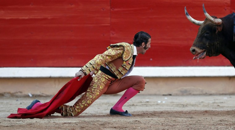 Spanish bullfighter Juan Jose Padilla kneels down in front of a bull during the last bullfight of the San Fermin festival in Pamplona July 14, 2012. Padilla lost an eye after getting gored last October during a bullfight in Zaragoza, northern Spain. He made a comeback five months afterwards. (Susana Vera/Reuters)
