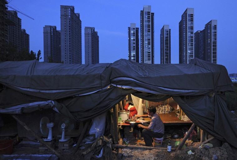 A laborer has his dinner under his shed at a construction site of a residential complex in Hefei, Anhui province, August 1, 2012. The average home price in China's 100 major cities edged up in July for the second straight month, reinforcing signs of a recovery in the property market even as the government seeks to spur broader economic growth, a private sector survey showed on Wednesday. (Reuters)