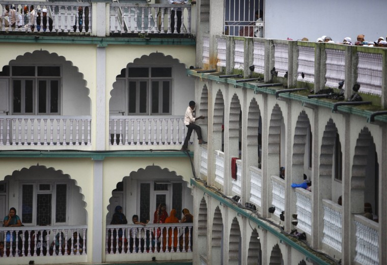 A latecomer climbs into the prayer hall of a crowded mosque for Eid al-Fitr mass prayers at Kashmiri Takiya Jame mosque in Kathmandu August 20, 2012. Nepali Muslims celebrate the festival of Eid al-Fitr, which marks the end of the holy month of Ramadan. (Navesh Chitrakar/Reuters)