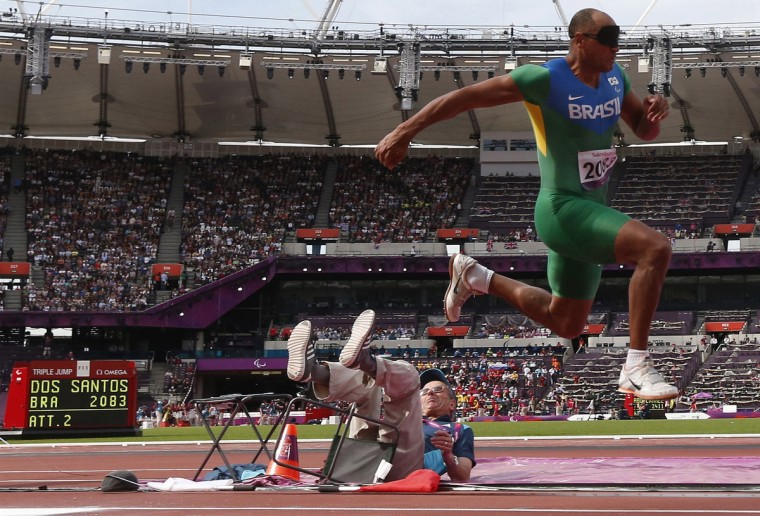 Brazil's Luciano dos Santos Pereira knocks over an official as he competes in the men's triple jump - F11 final in the Olympic Stadium at the London 2012 Paralympic Games September 6, 2012. Santos Pereira was competing against other athletes who were also visually impaired. (Suzanne Plunkett/Reuters)