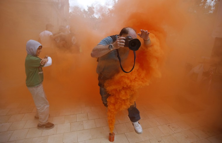 A photographer jumps over a smoke canister during a demonstration by firefighters, security and military personnel against cuts in their salaries imposed by Spanish Government, in the Andalusian capital of Seville September 29, 2012. Spain's debt will reach 90.5 percent of gross domestic product by end 2013 after hitting 85.3 percent of GDP by the end of this year, the government's budget document showed on Saturday. (Marcelo del Pozo/Reuters)