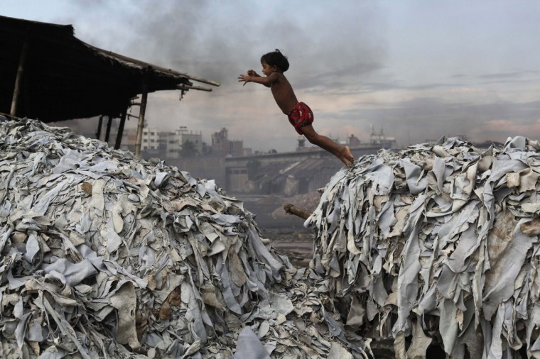 A child jumps on the waste products that are used to make poultry feed as she plays in a tannery at Hazaribagh in Dhaka October 9, 2012. Luxury leather goods sold across the world are produced in a slum area of Bangladesh's capital where workers, including children, are exposed to hazardous chemicals and often injured in horrific accidents, according to a study released on Tuesday. None of the tanneries packed cheek by jowl into Dhaka's Hazaribagh neighborhood treat their waste water, which contains animal flesh, sulphuric acid, chromium and lead, leaving it to spew into open gutters and eventually the city's main river. (Andrew Biraj/Reuters)