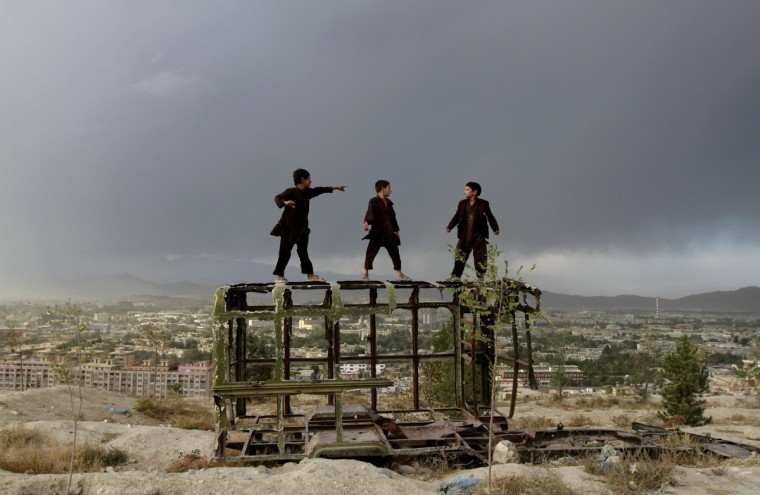 Afghan boys play on a destroyed car at a hilltop in Kabul October 18, 2012. (Mohammad Ismail/Reuters)