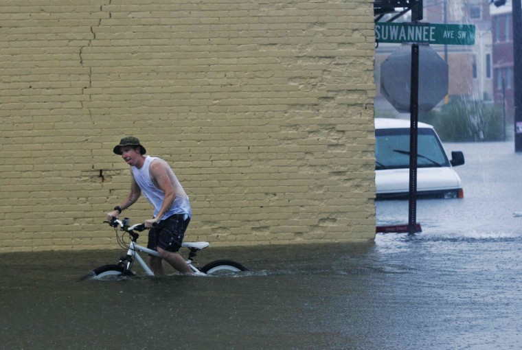 Phillip Roser struggles to pedal his bike in downtown Live Oak, Florida, June 26, 2012. Tropical Storm Debby drifted slowly eastward over Florida's Gulf Coast on Tuesday, threatening to dump more rain on areas already beset by flooding. After stalling in the Gulf of Mexico, the storm was finally moving but was expected to take two more days to finish its wet slog across Florida. (Phil Sears/Reuters)