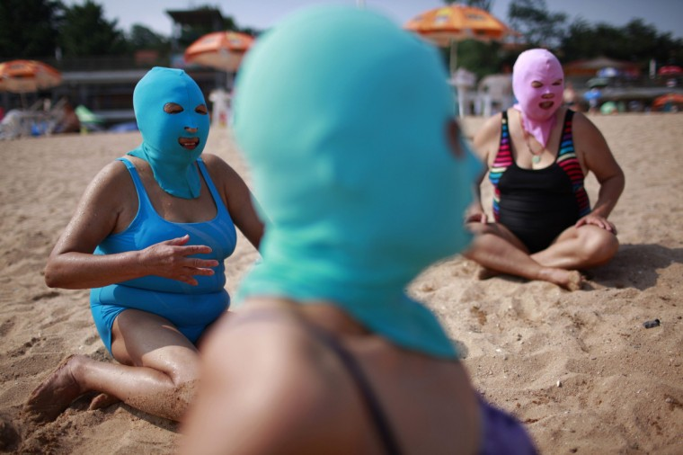 Women, wearing nylon masks, rest on the shore during their visit to a beach in Qingdao, Shandong province July 6, 2012. The mask, which was invented by a woman about seven years ago, is used to block the sun's rays. The mask is under mass production and is on sale at local swimwear stores. (Aly Song/Reuters)