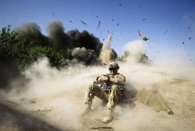 Jake Beaudoin, a U.S. Army Private of 508 BSTB, 4th Brigade Combat Team, 82nd Airborne Division, takes cover during a controlled detonation to clear an area for setting up a check point in Zahri district of Kandahar province, southern Afghanistan May 31, 2012. (Shamil Zhumatov/Reuters)