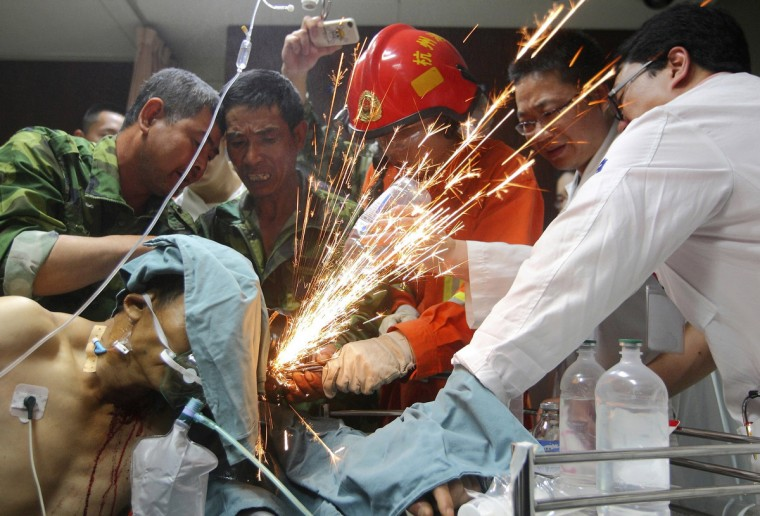 Workers, a firefighter and doctors work together to cut steel bars which were pierced through a worker's body at a hospital in Hangzhou, Zhejiang province, June 12, 2012. The worker was pierced by seven steel bars during his duty at a bridge construction site on Monday afternoon, local media reported. (Reuters)