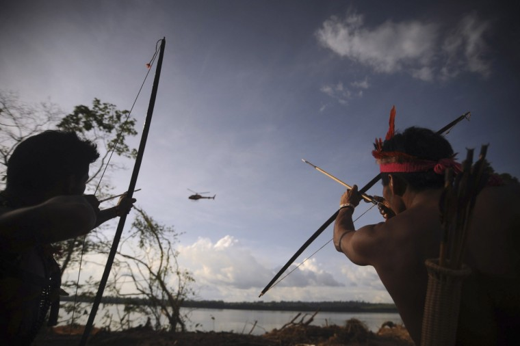 Indigenous people point their bows and arrows at a police helicopter flying over the occupied barrier of the Belo Monte Dam's construction site in Vitoria do Xingu, near Altamira in northern Brazil June 15, 2012. The area was occupied by around 300 activists, indigenous people, fishermen and coastal community members affected by the project as they protested against the construction of the Belo Monte Hydroelectric power plant, according to the activists. (Lunae Parracho/Reuters)