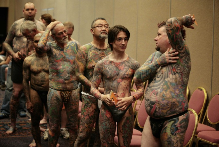 Jeff Bitting (R), from St Augustine, Florida, speaks back stage with fellow full-body tattoo contestants before judging at the National Tattoo Association Convention in Cincinnati, Ohio April 13, 2012. In his 33 years of getting tattoos, Bitting says he has had about 500 hours of work and will complete his other leg in his bid to win more full-body contests. Picture taken April 13, 2012. (Larry Downing/Reuters)