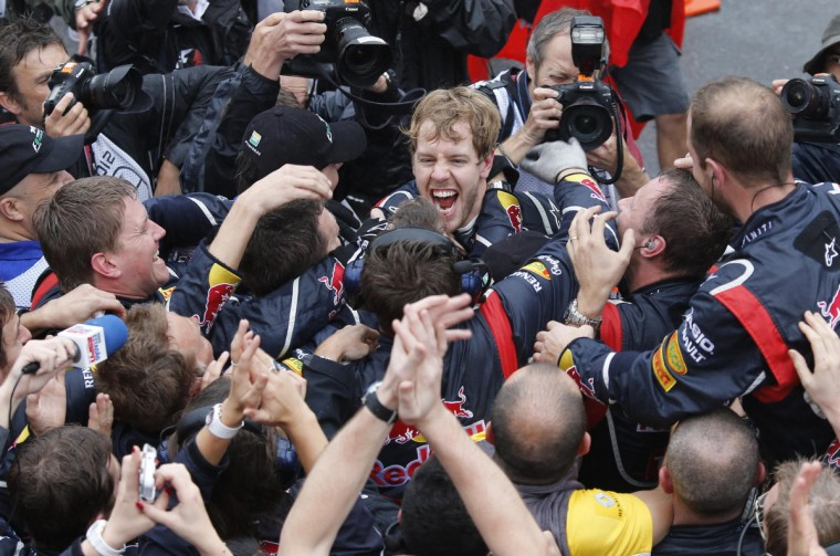 Red Bull Formula One driver Sebastian Vettel of Germany celebrates winning the world championship with his team after finishing sixth in the Brazilian F1 Grand Prix at Interlagos circuit in Sao Paulo November 25, 2012. Vettel became Formula One's youngest triple world champion at the age of 25 at the Brazilian Grand Prix on Sunday. (Sergio Moraes/Reuters)