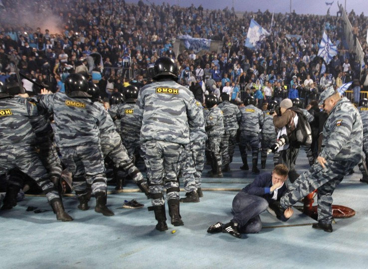 A riot policeman kicks a fan during clashes after the soccer match between Zenit and Dinamo Moscow in the Russian Premier league soccer match in St.Petersburg April 28, 2012.(Alexander Demianchuk/Reuters)